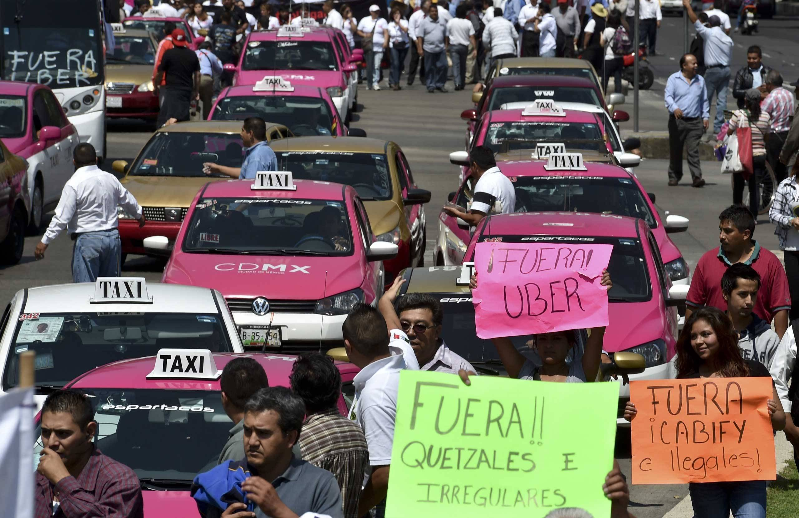 Taxi drivers take part in a protest against the private taxi company Uber for alleged unfair competition, in Mexico City on May 25, 2015. Thousands of taxi drivers protested across the Mexican capital to demand the government to take action against Uber, while the company retaliates by offering free transport in the city.   AFP PHOTO / Yuri CORTEZYURI CORTEZ/AFP/Getty Images